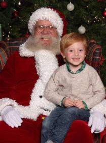 Happy young boy telling Santa his